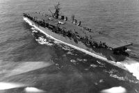 The U.S. Navy light aircraft carrier USS Langley (CVL-27) underway off Cape Henry, Virginia (USA), with two North American SNJ Texan training planes on her flight deck, 6 October 1943.
